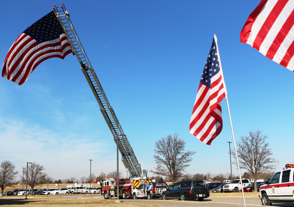 Flags wave above a hearse at a funeral service for John Randle, a firefighter at Wamego Middle School in Wamego, Kansas on Jan. 6, 2018.