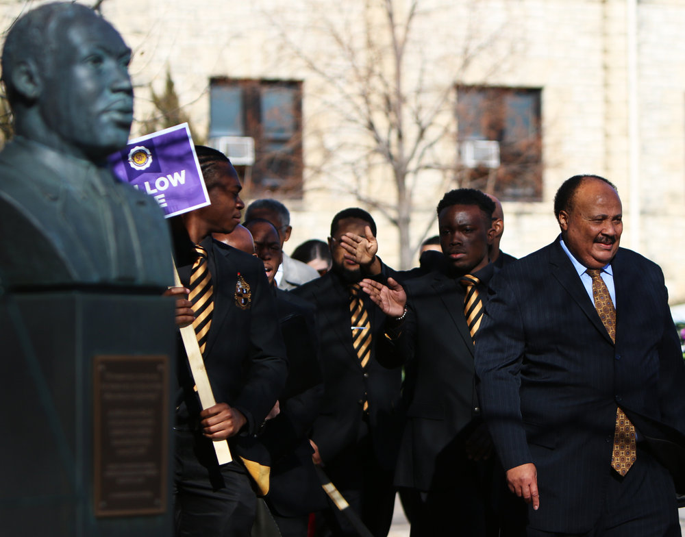 Members of Alpha Phi Alpha follow Martin King Luther III to a wreath-laying ceremony at K-State's Martin Luther King Jr. bust following a lecture by Martin Luther King III on Jan. 25, 2018.