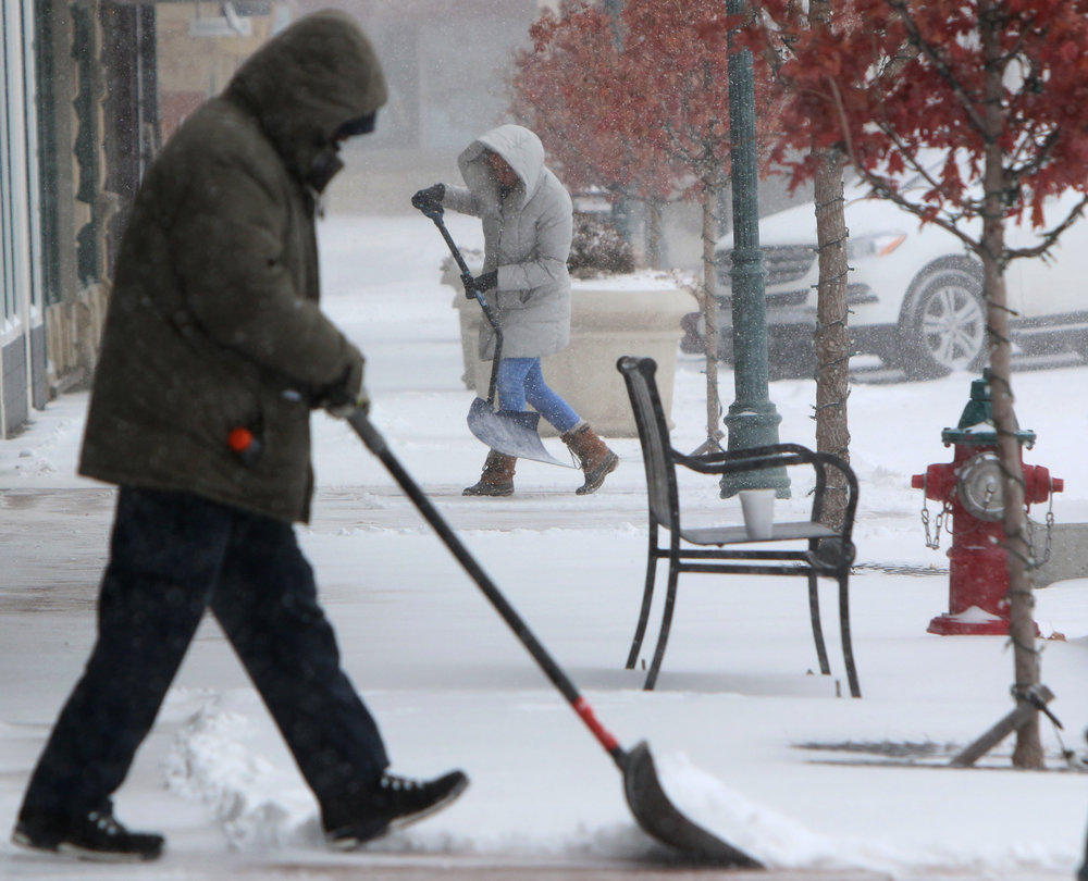 After Eckles, left, and Katie Stone shovel snow downtown on January 1, 2018.