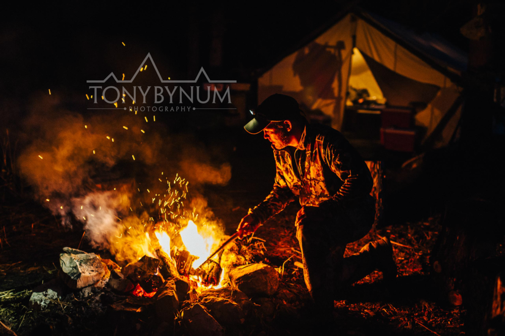 A hunter stirs a fire in front of the camp tent in the rocky mountains. © Tony Bynum