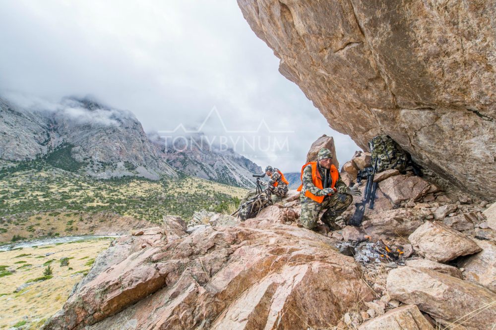 Two hunters on a mountain cliff face warming by a fire and glassing for mule deer in wyoming. © Tony Bynum