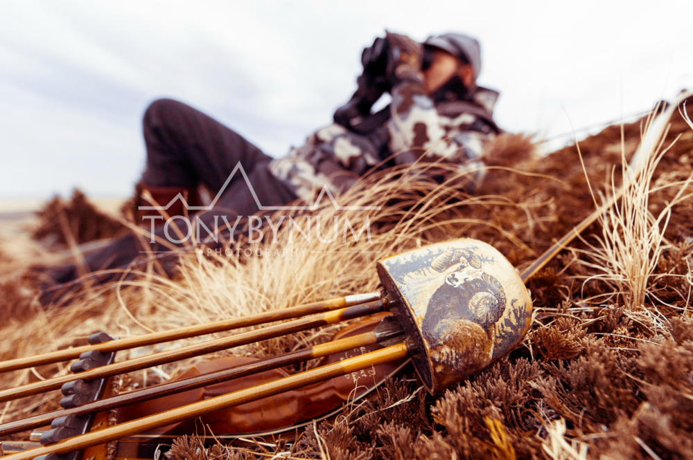 A hunter glassing for wild bighorn sheep with his traditional recurve bow and custom quiver. © Tony Bynum