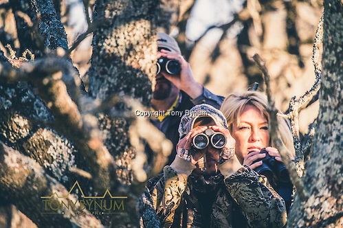 Hunters using their binoculars to spot game using a tree for cover. La Pampa, Argentina ©tonybynum.com
