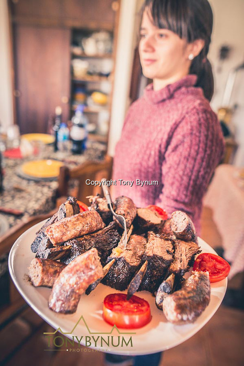Serving a plate of BBQ meat and sausage. La Pampa, Argentina ©tonybynum.com