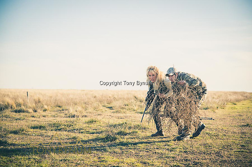 Hunter and guide use a large tumble weed for cover as they approach a red stag. La Pampa, Argentina ©tonybynum.com