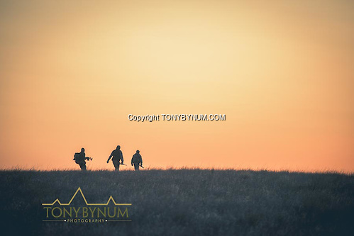 Hunters crossing the open prairie grasslands at first light. La Pampa, Argentina ©tonybynum.com