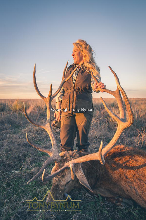 A woman with her large, free range, trophy stage taken on the Los Molles Ranch. La Pampa, Argentina ©tonybynum.com