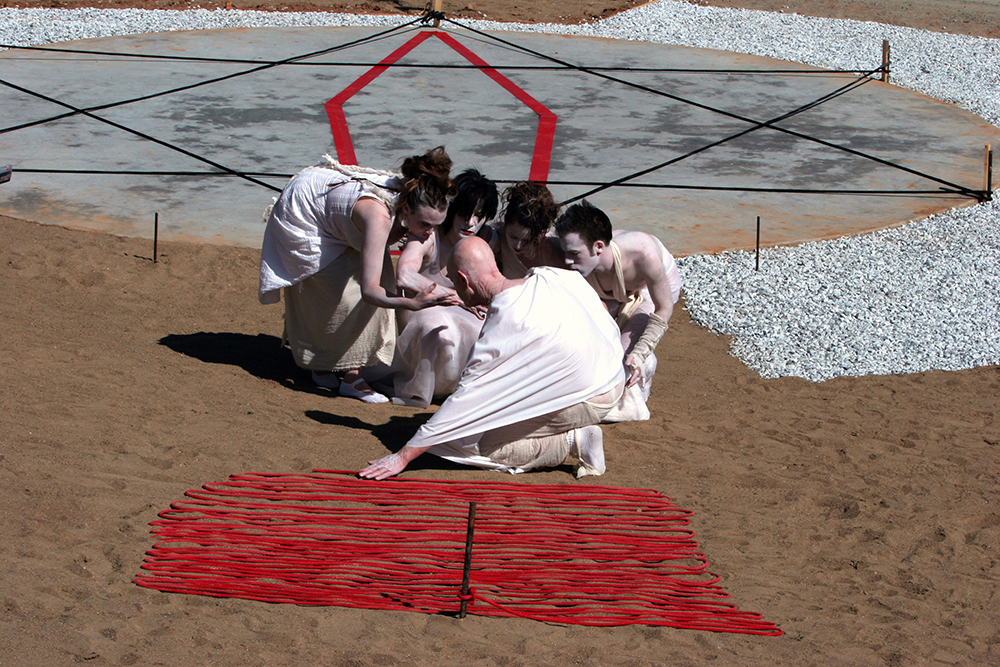 """Pentagon VS Hexagon"", performance still. © 2005 Tom White with Betty Jo Costanzo and Styrous Butoh Drawing is a continuation of our previous artistic and teaching developments in which drawing, painting, video and performance are tools for recognizing, isolating, and relaying shapes and patterns which are generated perceptually. This isolation is designed to reveal spatial relationships not dependent on linear scrutiny, but rather, moving through the perceptual field to understand collective creation. Traditionally, drawing and painting have conveyed images which refer to subjects such as allegories, portraits, landscapes, still lifes. As postmodern artists, we seek new definitions of drawing and painting which liberate the art spirit to convey traditional images as well as text, universal archetypes and the recording of the processes which venture outside the art world, into the communities and cultures which may create new archetypes, symbols and mythologies. Through the use of Butoh collaboration we wish to further investigate and use the visual focus and concentration necessary in producing definitions which generate new drawing and painting. Although Butoh has evolved as a dance form, we use its disciplines to reacquaint the individual with a strong awareness of the five senses, promoting a perception of a wider field. This fosters creative actions and formations of decisions and protocols which are artistic and contain a quality of economy proving more beneficial than those achieved through linear means alone. While we work together in our studio, we begin with exercises which emulate moving meditation. These exercises allow us to begin our Butoh Walk, which is a discipline or regimen of exercises leading to our state of visual focus and heightened sensory awareness of the peripheral field. It enables us to begin our unique from of Butoh Drawing. Butoh Drawing is inspired by the innovative works of such artists as Cezanne, Mondrian, and Bill Viola. John Cage challenged mid-century modernism by replacing aesthetic decisions with chance operations determining form. The history of Butoh Dance begins with Hijikata followed by Ohno and Kasai. In our individual work previous to Butoh Drawing, we each have experimented with the ingredients now affirmed by our studies with Akira Kasai and his protégé Setsuko Yamada. ""Butoh, a Japanese indigenous dance form, is not only performance, but also the embodiment of one of the most precise critical spirits in the history of the consciousness of the body, with a strength of thought which impinges deeply on the history of the human spirit Butoh's actual existence was the imprint left by the potent ideas of Tatsumi Hijikata. The understanding of the body in butoh makes it possible, through the body to give expression even to a flesh ravaged by age and illness, in what at first glance is apparently an enlargement and deepening of the concept of dance. When the style first appeared, Hijikata Tatsumi, himself called it Ankoku Butoh (Dance of Darkness). He founded Butoh with the collaboration of a small number of dancers and artists. Since then, Hijikata's Theory of Butoh has had a comprehensive effect on contemporary arts in general"" (Butoh in the Late 1980's by Kazuko Kuniyoshi with translation by Richard Hart). © 2008 Tom White and Betty Jo Costanzo"