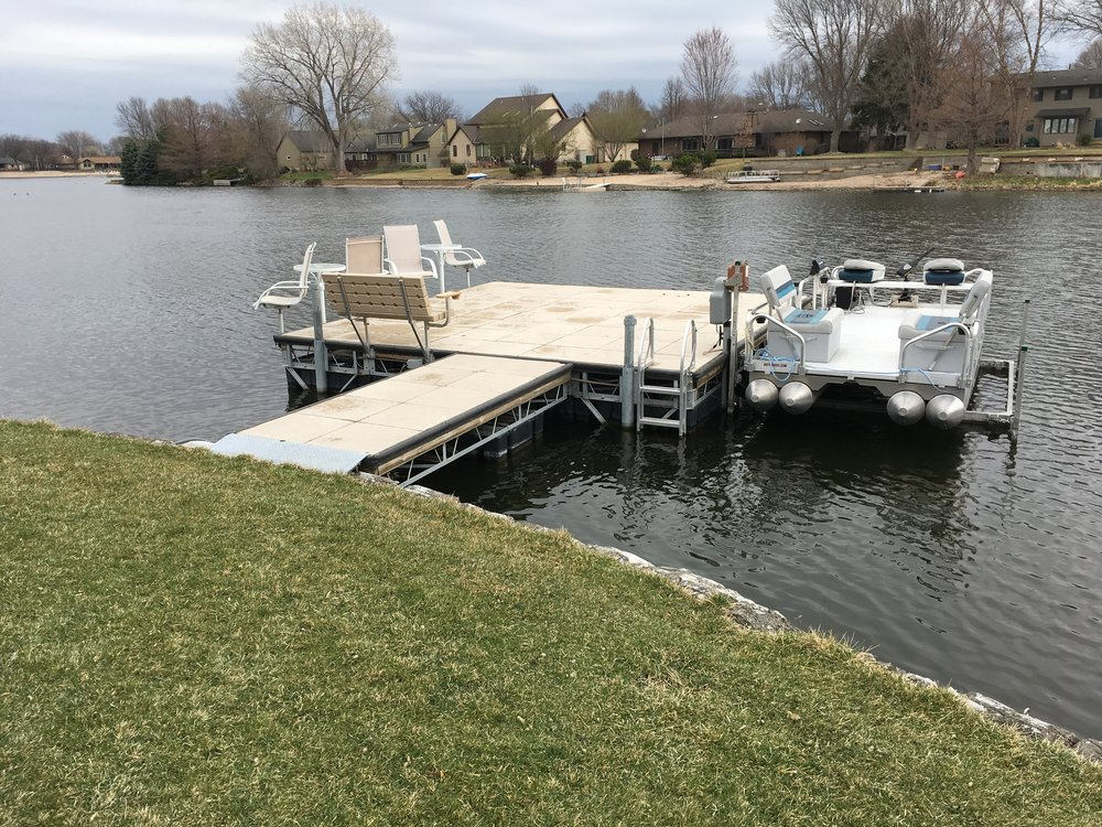 Shoremaster concrete dock with furniture and boat lift. Hotwood's 615 Aluma Sport pontoon. Installed in Grand Island, Nebraska by Hotwoods.