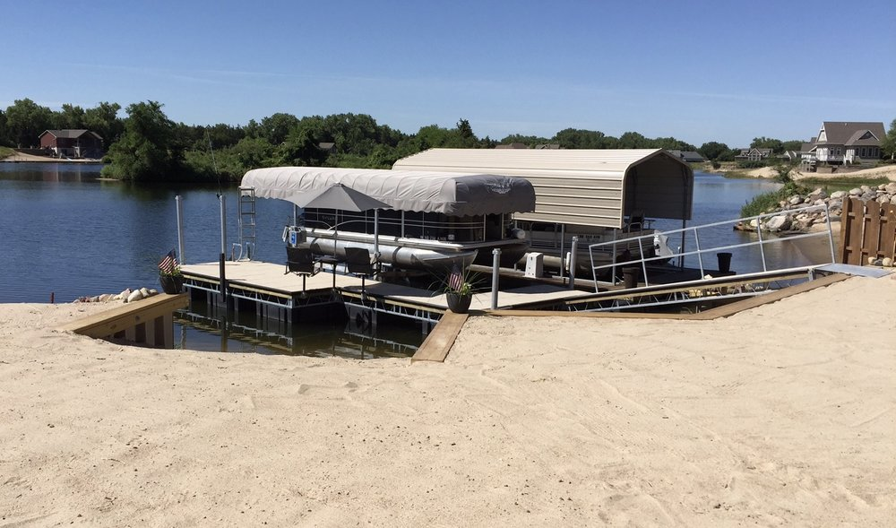 Shoremaster concrete dock and aluminum boat lift complete with furniture, umbrella, ladder and cover on the lift, installed by Hotwood's crew in Clarks, Ne. This is a true extension to your property.