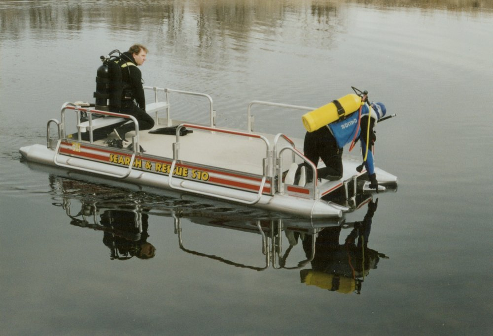This is a Fish N Sport set up as a Search & Rescue pontoon boat used by the very team that helped us develop this type of boat in our early years of production.  All decals are reflective to be seen at a great distance at night if the dive is to be done during the night time hours.  The side rescue rails were also developed in conjunction with this team to be used as a quick grab point on both sides of the boat if needed when coming up out of the water. They also work great for multiple men to grab and go when it comes to carrying the boat across an area that does not have a boat ramp to get the craft into the water.  The front dive deck that the man is working from also is a great place to have your rescue dog if your team uses a dog for water rescues.   Any of Hotwood's pontoon boats we manufacture can be set up with the Search & Rescue reflective decals like the Fish N Sport shown above and below.