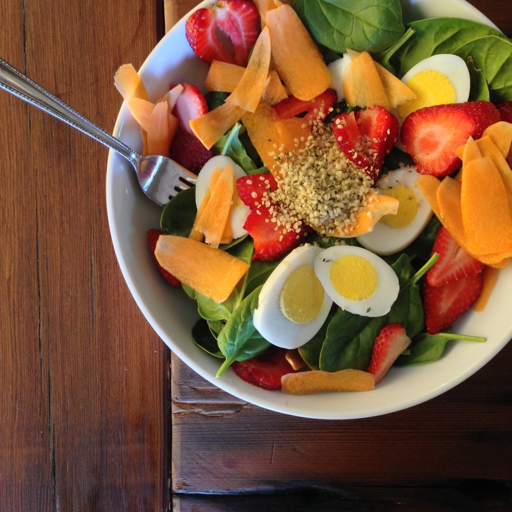 Garden leafy greens, carrot ribbons, strawberry slices, hard-boiled eggs, hemp seeds