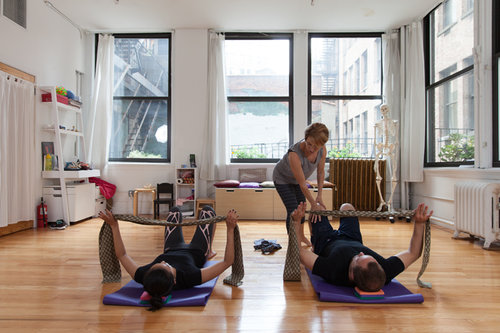 Two actors go through an Alexander Technique floor exercise with fabric straps to learn about support. Belinda assists.