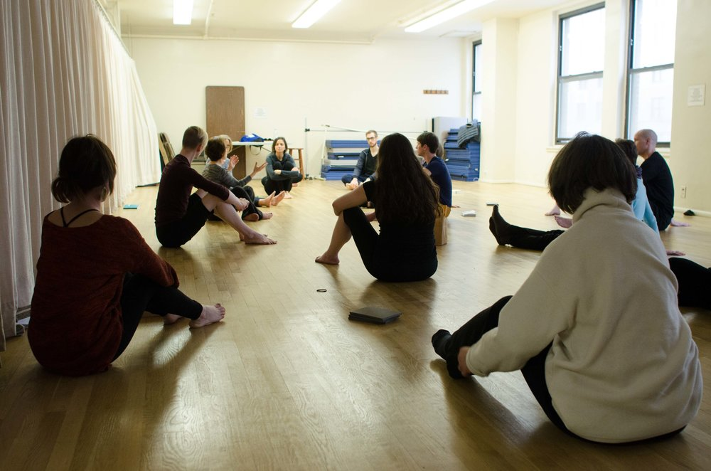 Belinda teaches Alexander Technique to a group class. Students sit on the floor listening to instruction while Belinda teaches in an airy Manhattan studio.