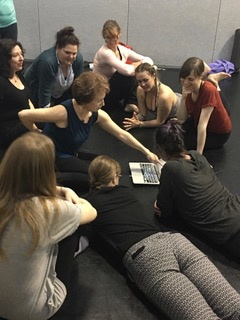 Belinda teaches Alexander Technique to a group of students on the floor of a studio. The students gather around Belinda to look at her explaining a diagram of the human anatomy.