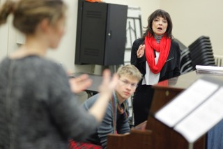 Vicki Shaghoian teaches a musical theatre singing masterclass at Yale School of Drama. A Singer sings in front of class with a music stand in front of her while Vicki instructs in the background.