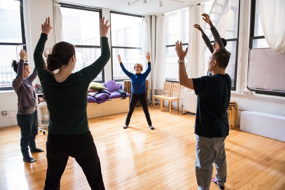 Belinda leads a group Alexander Technique exercises for a group of 4 actors. They expand their bodies and energy while standing upright. Class takes place in a Flatiron NYC studio with wooden floors and open space.