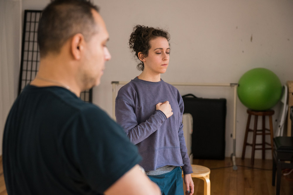 Two actors, a woman and a man, stand with their right hand over their chest and their eyes closed in an open NYC movement studio.