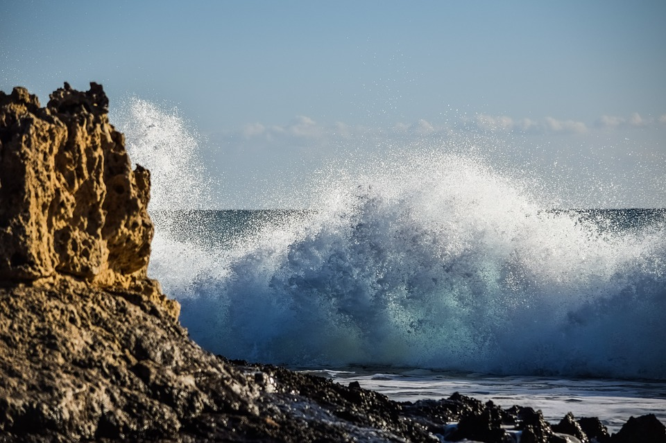 A big wave hitting a rocky shore.