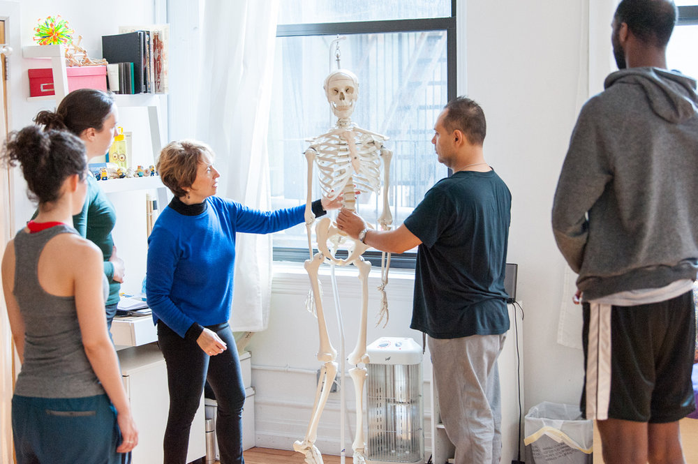 Belinda teaching an Alexander Technique to a group of actors. She demonstrates the thickness of the spine by have students hold a skeleton's spine in their hand to know they have strength and support.