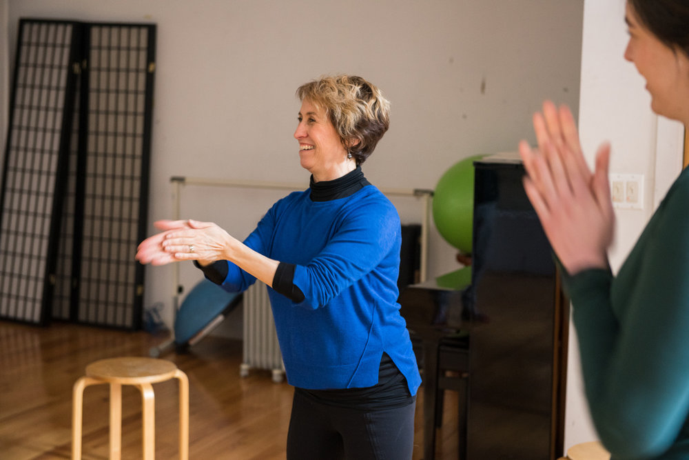 Belinda Mello teaches the Alexander Technique to a group of actors. She rubs her hands together and smiles teaching her students about the use of energy. A student smiles in the right side of the picture.
