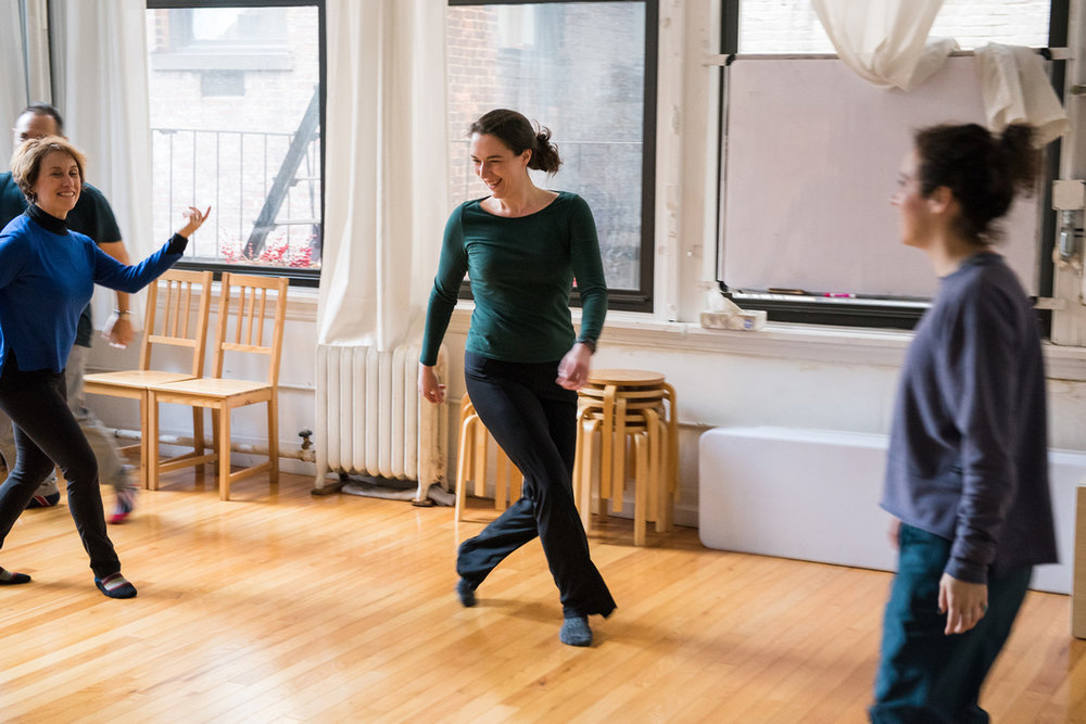 Belinda teaches and Alexander Technique group class to a couple of actors. They go through Alexander Technique exercises to experience ease in movement. a group of actors move joyously around the studio connecting with each other.