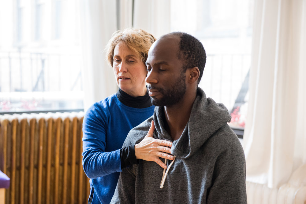 Belinda guides an actor through a chair exercise using the Alexander Technique in her NYC Studio.Her hand is on the actors chest and upper back helping him feel how much depth he has.