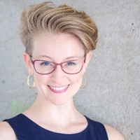 Headshot of Dana Calvey, New York City Alexander Technique teacher and Guest Instructor at AT Motion Center for Actors. Dana has short blonde hair, pink framed glasses, and smiles at the camera.
