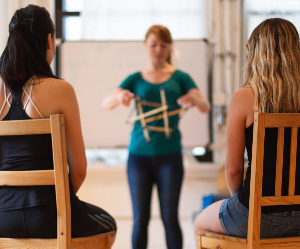Holly Cinnamon, Guest Alexander Technique Teacher at AT Motion Center for Actors, teaching a student with her hands on the students ribs helping the student how her ribs move while breathing.