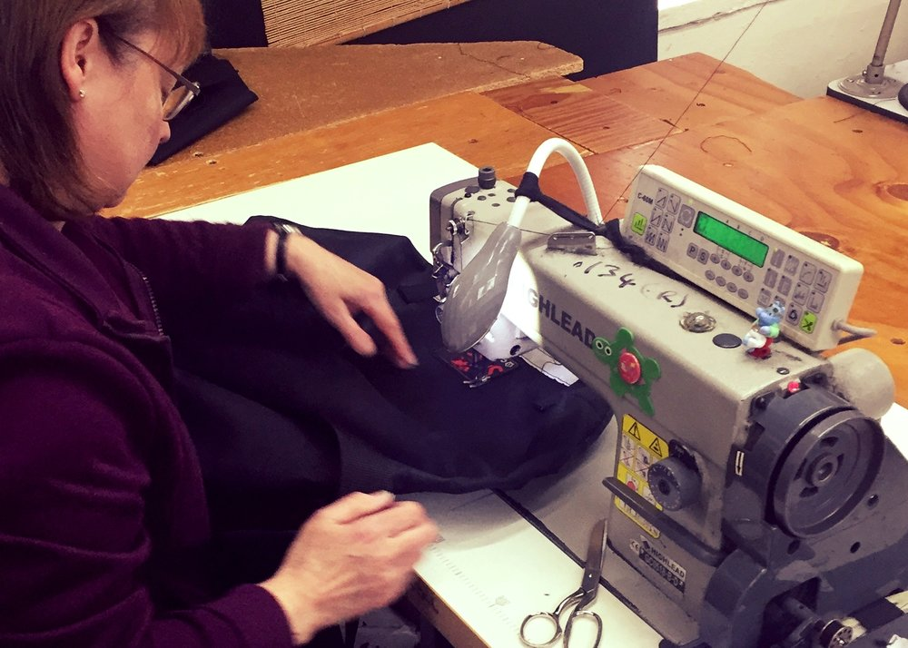 Master-craftswoman Sue putting the finishing touches on a Super C Courier Bag.