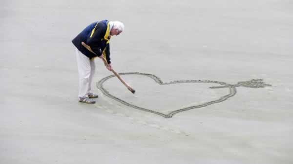old man drawing a heart in the sand with a stick by himself