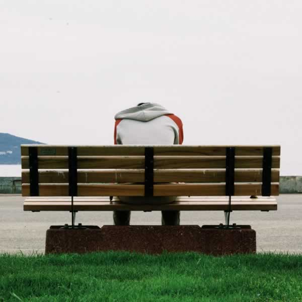man sitting on a bench with his head down.