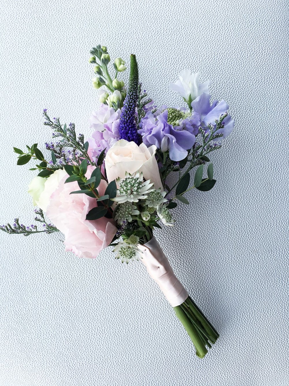 Bridesmaids Posies comprises of sweet pea, roses, astrantia, veronica, matthiola, caspia purple to name a few. Simple with a touch of sweetness to accompany the bride's bouquet.
