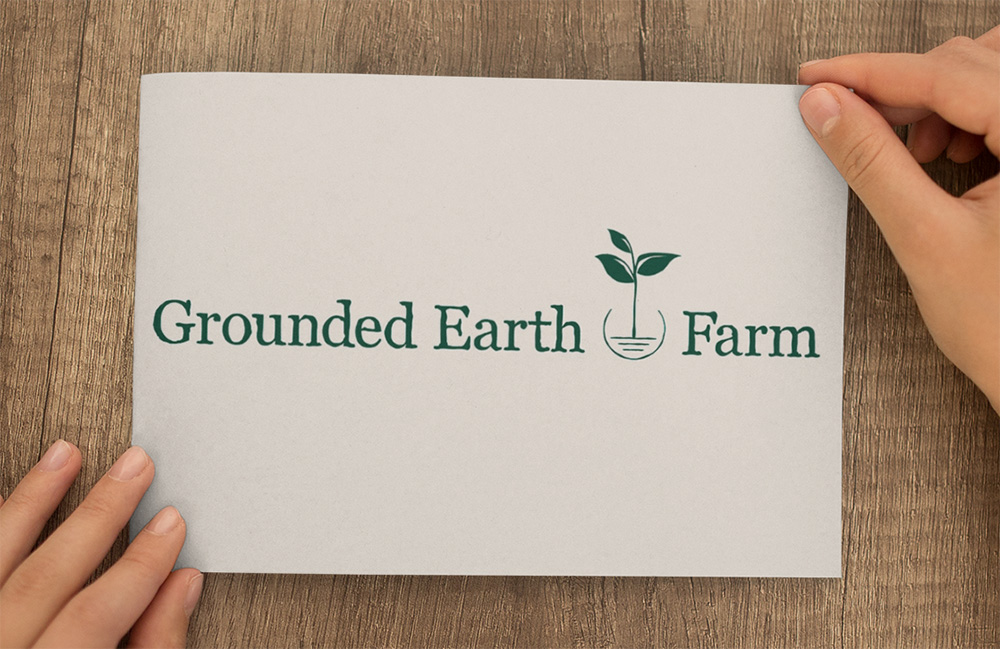 Sustainable Farm Logo - Grounded Earth FarmWe designed this farm logo for a husband and wife team starting a new family farm. The husband is a union electrician, and the concept of grounding is central to their partnership and farm brand. They wanted to incorporate the universal symbol for grounding in the logo, which we did through the seedling shape with the three lines beneath.