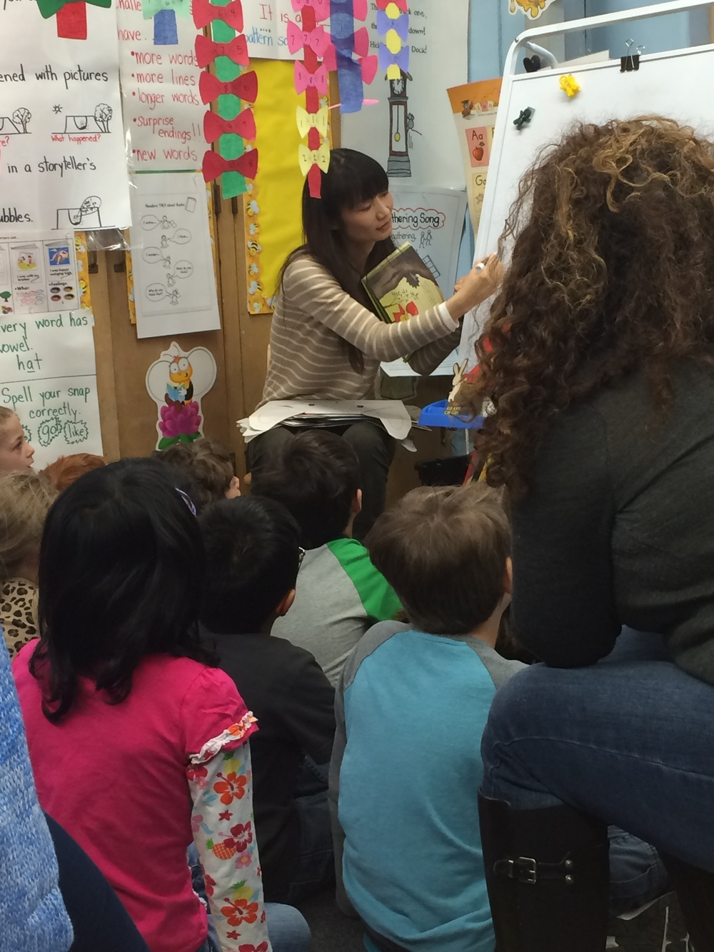 Naoko Stoop demonstrates her illustration technique to a class of kindergarten students.