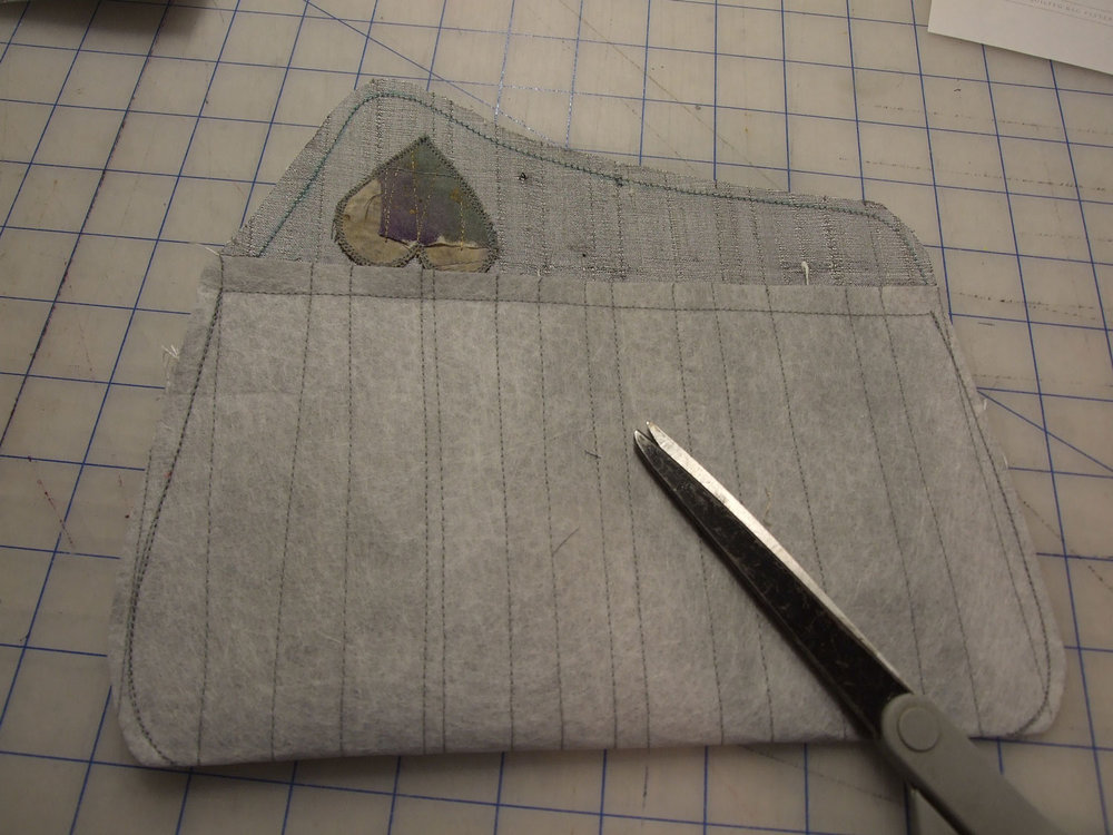 . Stitch the heart to the front of the flap . Fold the clutch along the bottom, right sides together, and stitch the side seams; trim and clip as needed . Similarly sew the side seams of the lining . Sew the lining to the silk along the front and flap edges of the purse (refer to the pattern for detailed instructions)