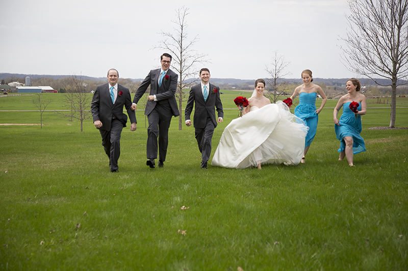 little-log-house-pioneer-village-hastings-minnesota-wedding-party-running-field-blue-bridemais-dresses-red-flowers-melanie-mahonen-photography