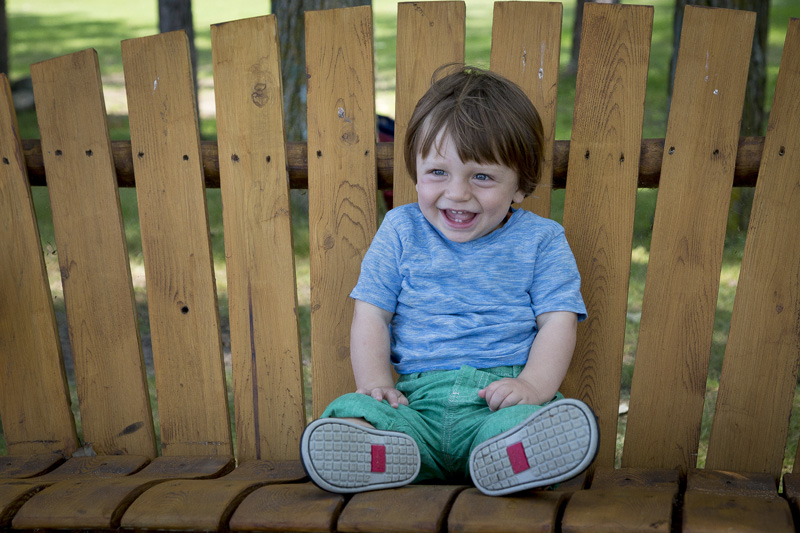09-one-year-boy-portrait-family-cabin-session-swing-happy-melanie-mahonen-photography