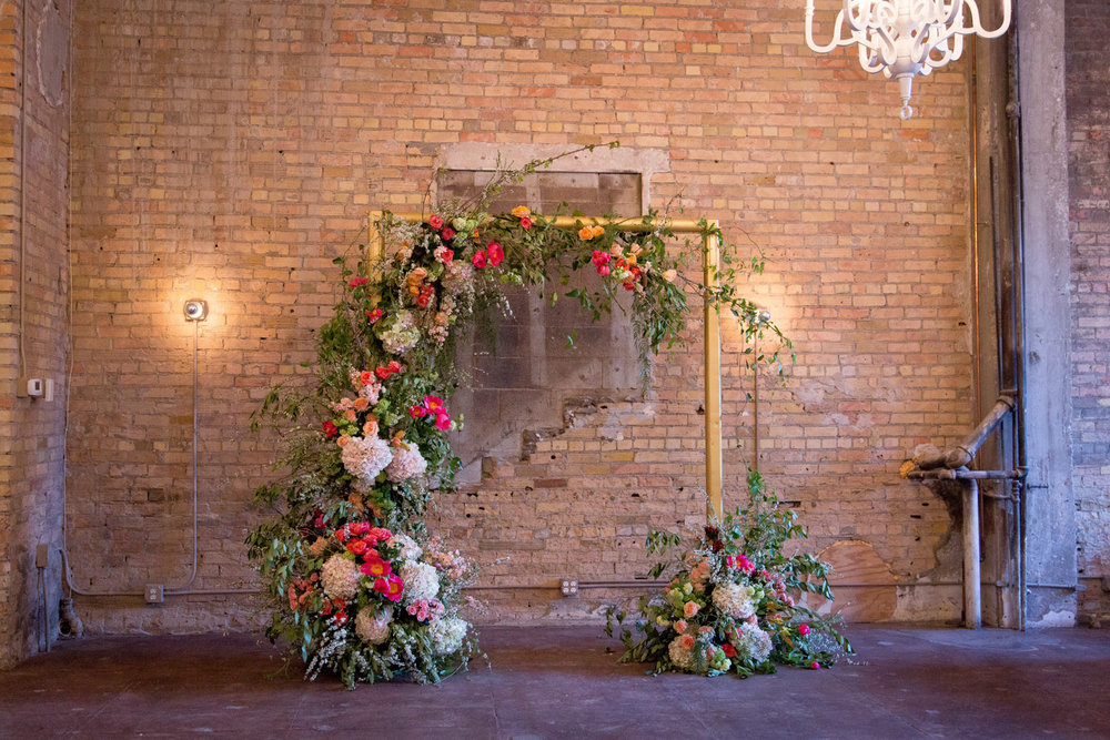 20-gold-floral-wedding-ceremony-arch-brick-wall-loring-social-mineapolis-minnesota-mahonen-photography.jpg