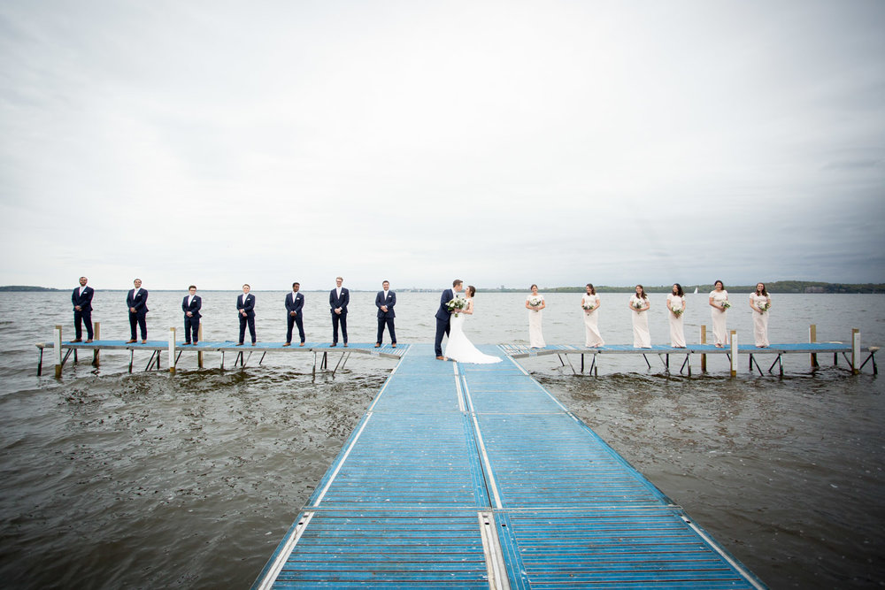 08-bishops-bay-country-club-middleton-wisconsin-wedding-party-group-portrait-lawn-dock-lake-mendota-navy-blue-suits-pale-pink-bridemaids-dresses-mahonen-photography.jpg