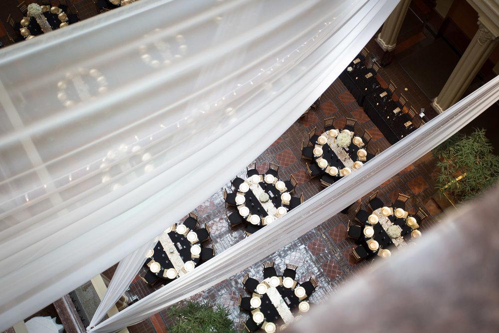 18-the-landmark-center-st-paul-mn-wedding-photographer-reception-table-settings-black-gold-charger-plates-linen-effects-drapery-mahonen-photography.jpg
