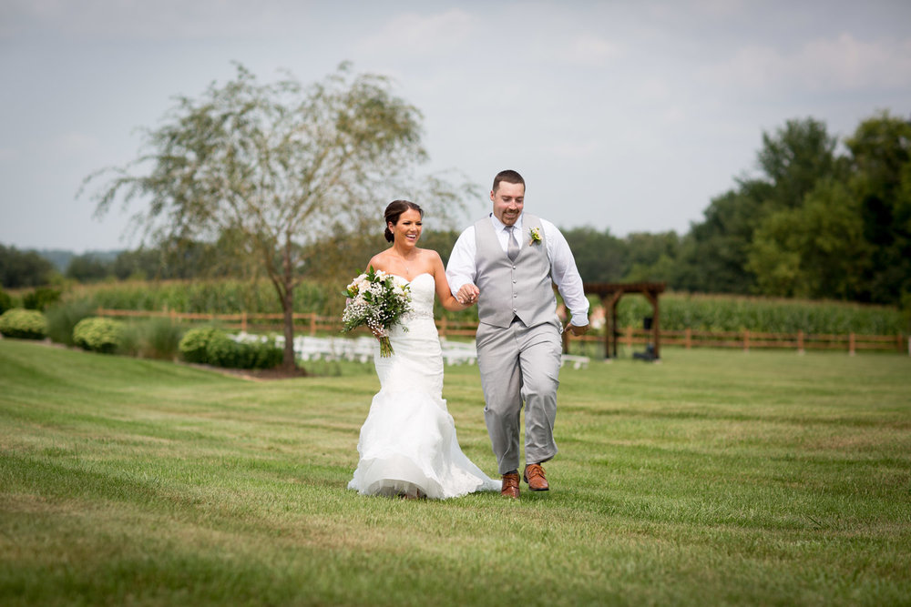 14-ridgetop-prescott-wisconsin-wedding-photographer-bride-and-groom-informal-portraits-skipping-grassy-field-mahonen-photography.jpg