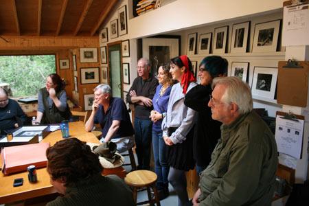 Richard Midthun listening while Kim Weston shows prints