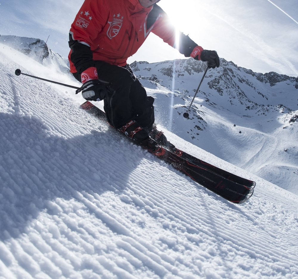 Close up of skier making a ski turn on fresh groomed snow.
