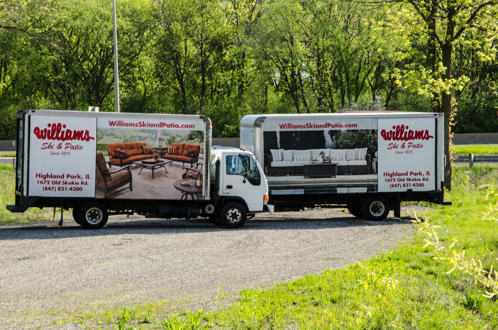 Williams patio furniture delivery trucks parked by highway with green trees in background.