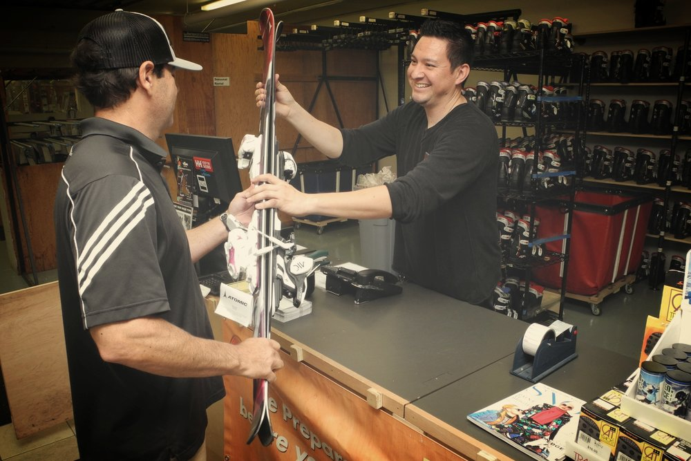 Williams Ski & Patio ski service team member taking customer skis at Williams ski service counter.