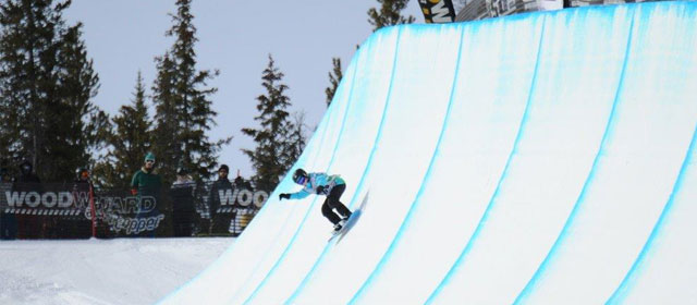 Girl Snowboarding in half pipe.
