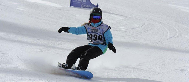 Female snowboarder making carving turns through gates.