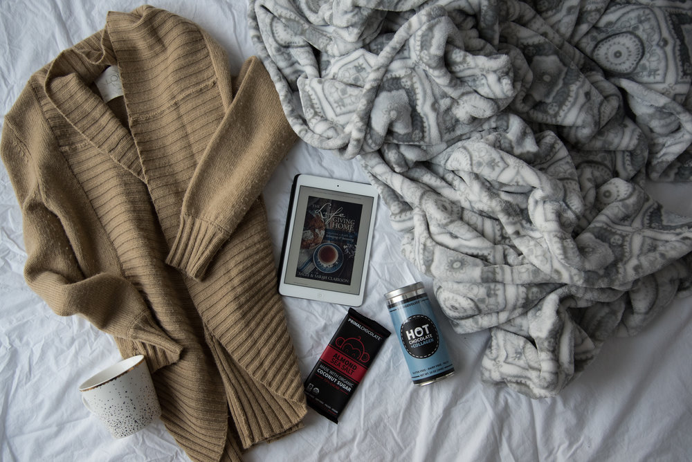 Hygge Faves:  A cozy sweater, a pretty mug, yummy treats, a good read, and a snuggly blanket.