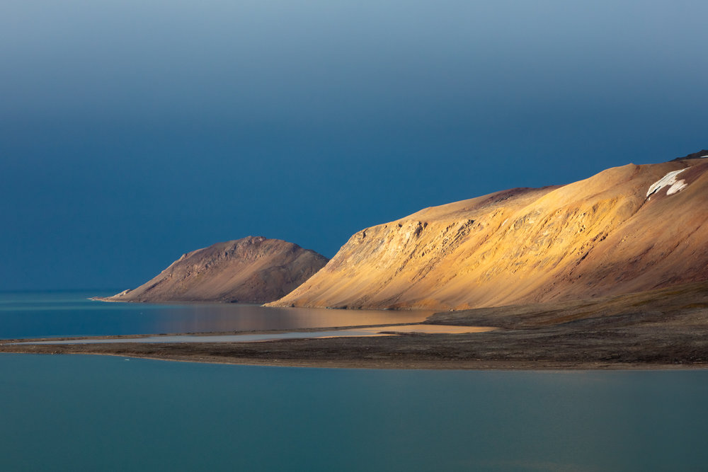 An isolated beam of sunlight peeks through a small hole in a heavy rainstorm, illuminating the barren hillsides of Svalbard's north coast like a golden spotlight. There is something magical about the late-summer light in the high arctic. The sun never fully sets, but rather circles the horizon, creating a sunrise and sunset that lasts all day. Just minutes before, in the thick of the torrential rainstorm, the landscape appeared dark and colorless. As the sun made its brief appearance, I stood in awe as one of the most vibrant scenes I have ever witnessed emerged from the darkness.